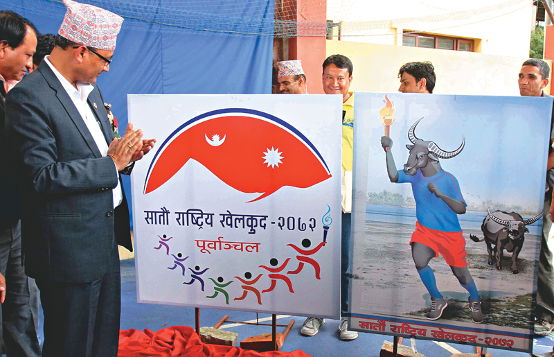 Youth and Sports Minister Purushottam Paudel looks at the logo (left) and mascot of the seventh National Games at the nOlympian semi-covered hall in Kathmandu on Friday. Photo : THT