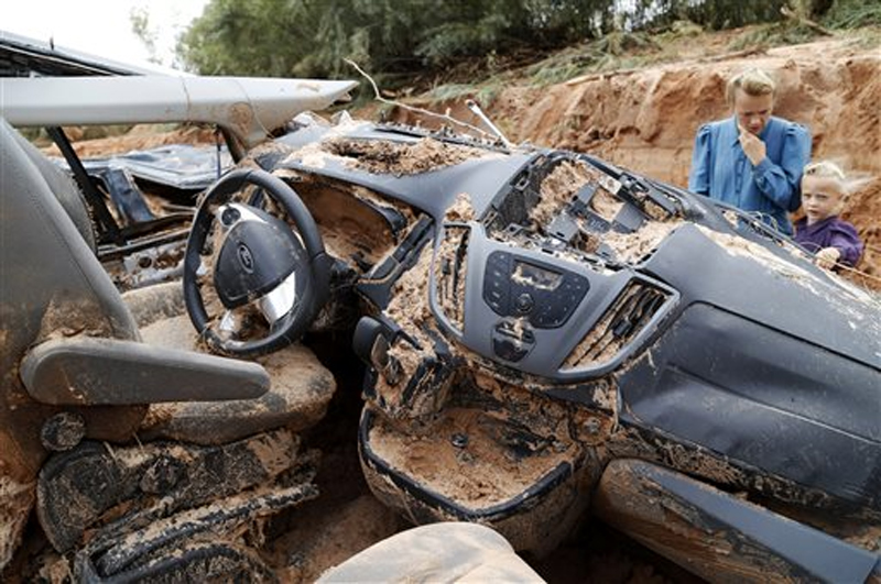 A woman and child examine a vehicle swept away during a flash flood, Tuesday, Sept. 15, 2015, in Hilldale, Utah. Photo: AP