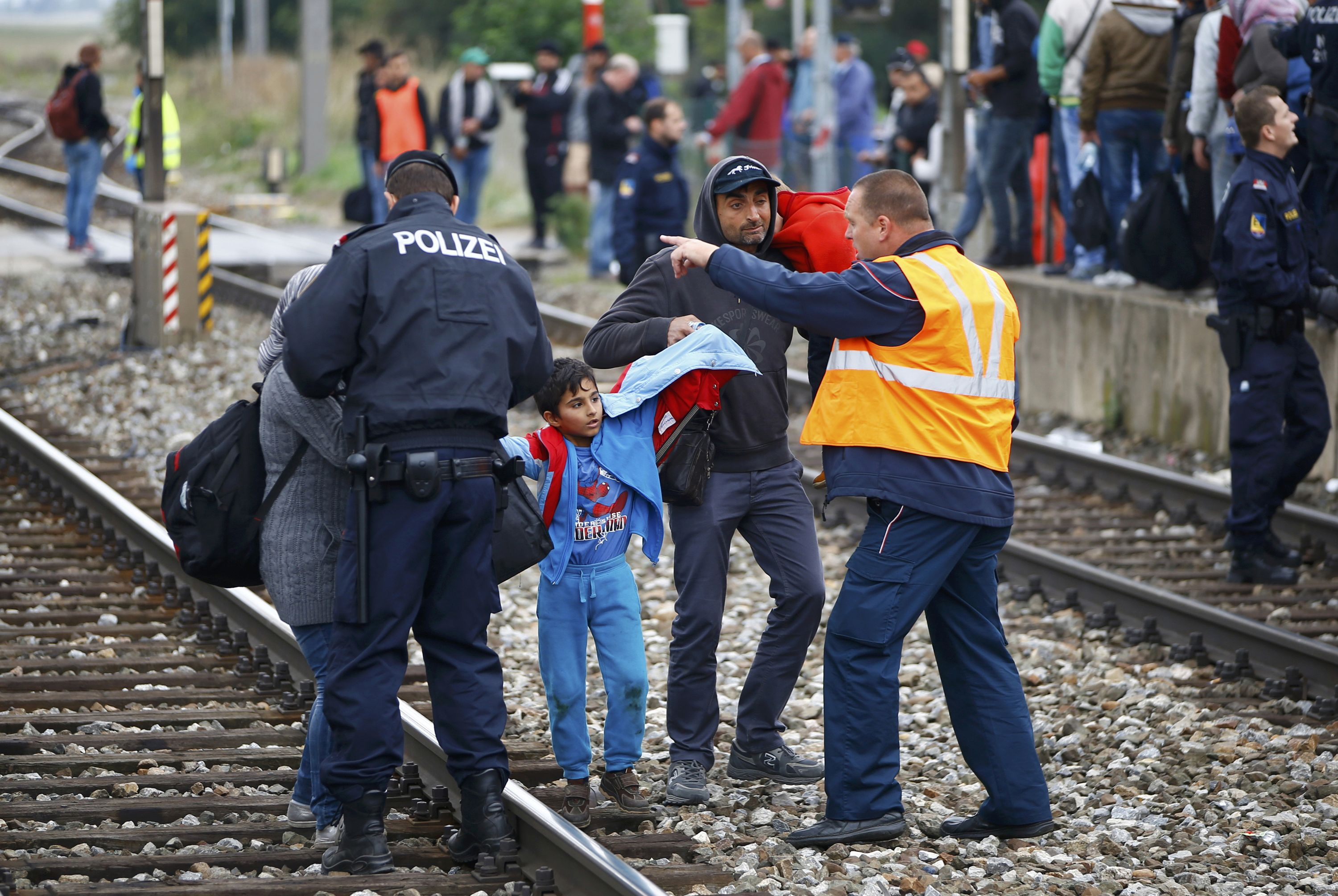 A policeman and a railway worker attempt to keep migrants off the rail track at the train station in Nickelsdorf, Austria, September 11, 2015. The train link between Austria and Hungary will remain closed through the weekend because of the continued strain on the system from the large inflow of migrants, the Austrian rail operator OeBB said in a statement on Friday. REUTERS/Leonhard Foeger