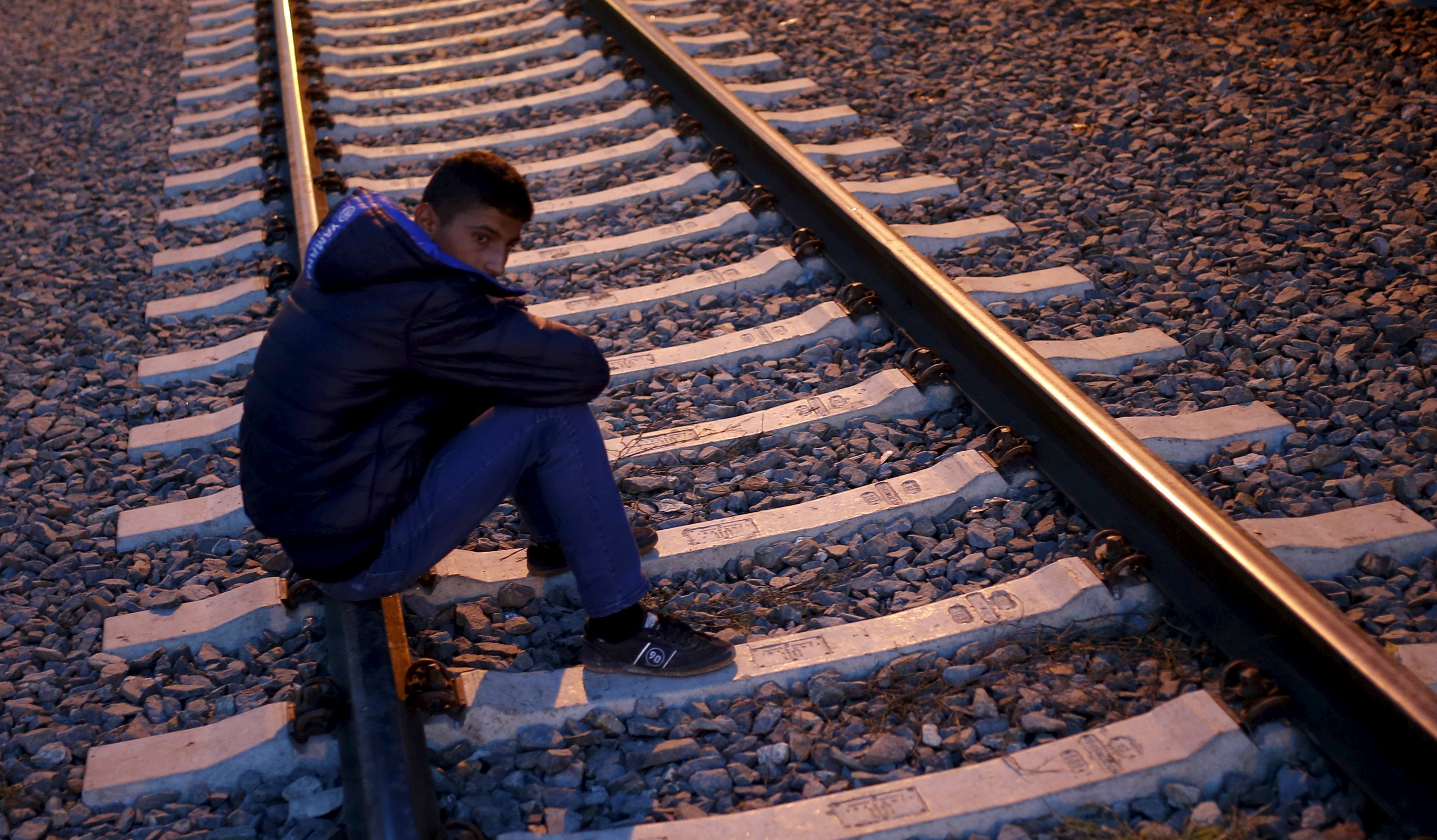 A migrant sits on the tracks as others board a train at the railway station in Tovarnik, Croatia October 2, 2015.  REUTERS/Dado Ruvic