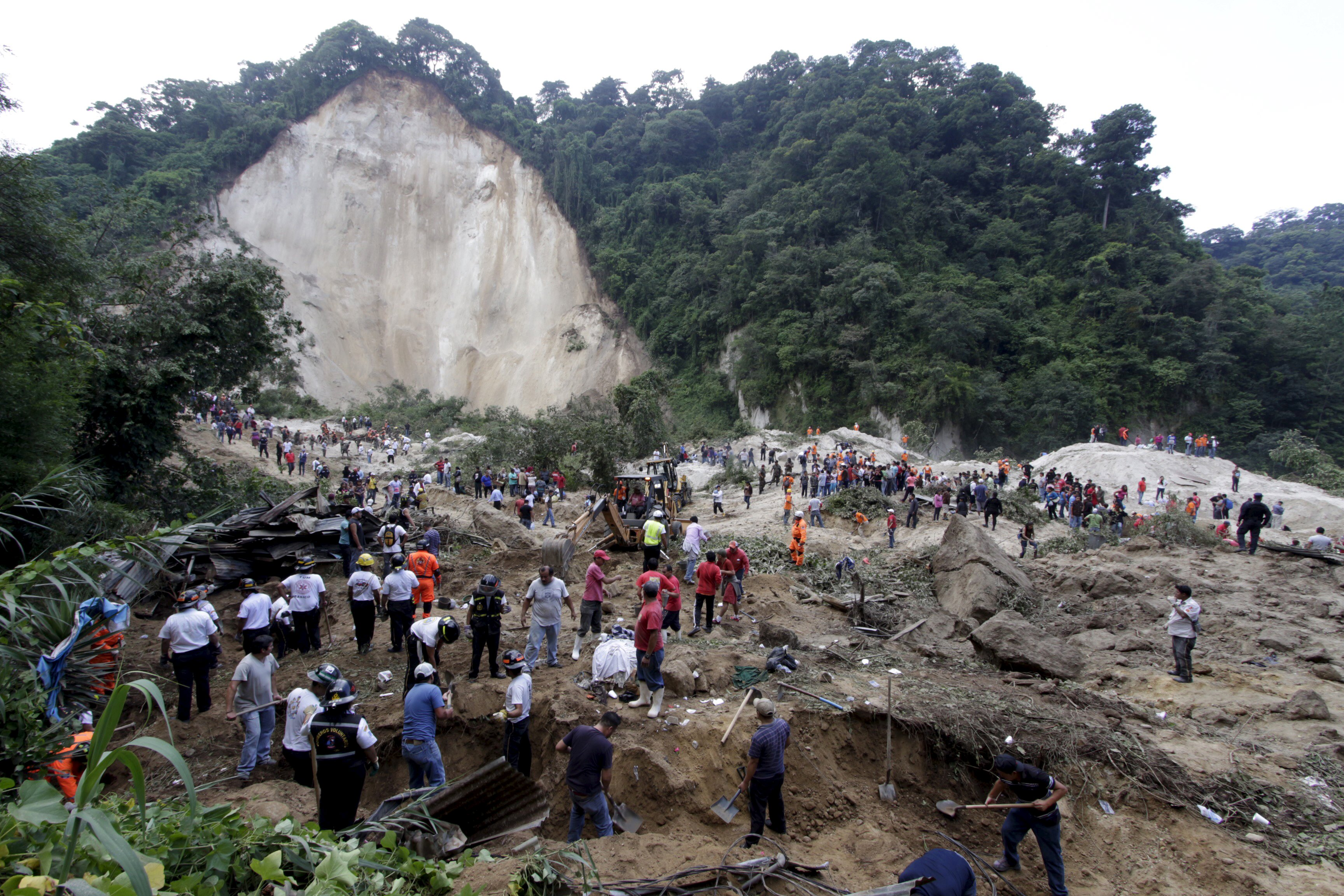 Rescue team members and volunteers search for mudslide victims in Santa Catarina Pinula, on the outskirts of Guatemala City, October 2, 2015. Hundreds of rescue workers dug through sludge and rock on Friday looking for survivors of a massive mudslide in Guatemala that killed at least nine people and left as many as 600 missing, burying homes in a town on the edge of the capital. Heavy rains swept a torrent of boulders and mud over dozens of homes on Thursday night in Santa Catarina Pinula on the southeastern flank of Guatemala City, one of the worst mudslides to hit the poor Central American country in recent memory. REUTERS/Josue Decavele      TPX IMAGES OF THE DAY