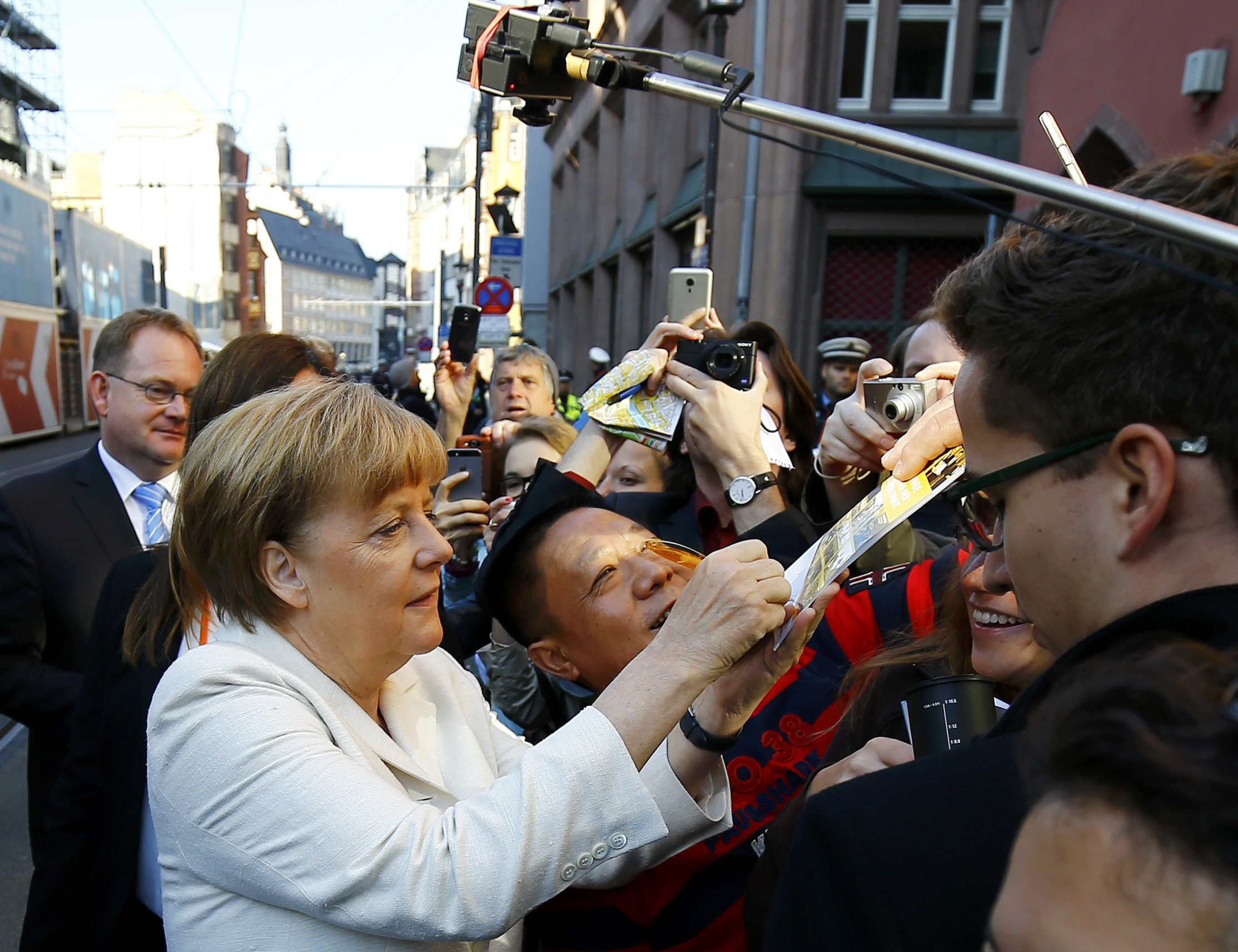 A man takes a selfie as German Chancellor Angela Merkel signs an autograph in Frankfurt, Germany, October 3, 2015. Germany's political leaders celebrate the country's 25th anniversary since the reunification of East and West Germany.   REUTERS/Kai Pfaffenbach