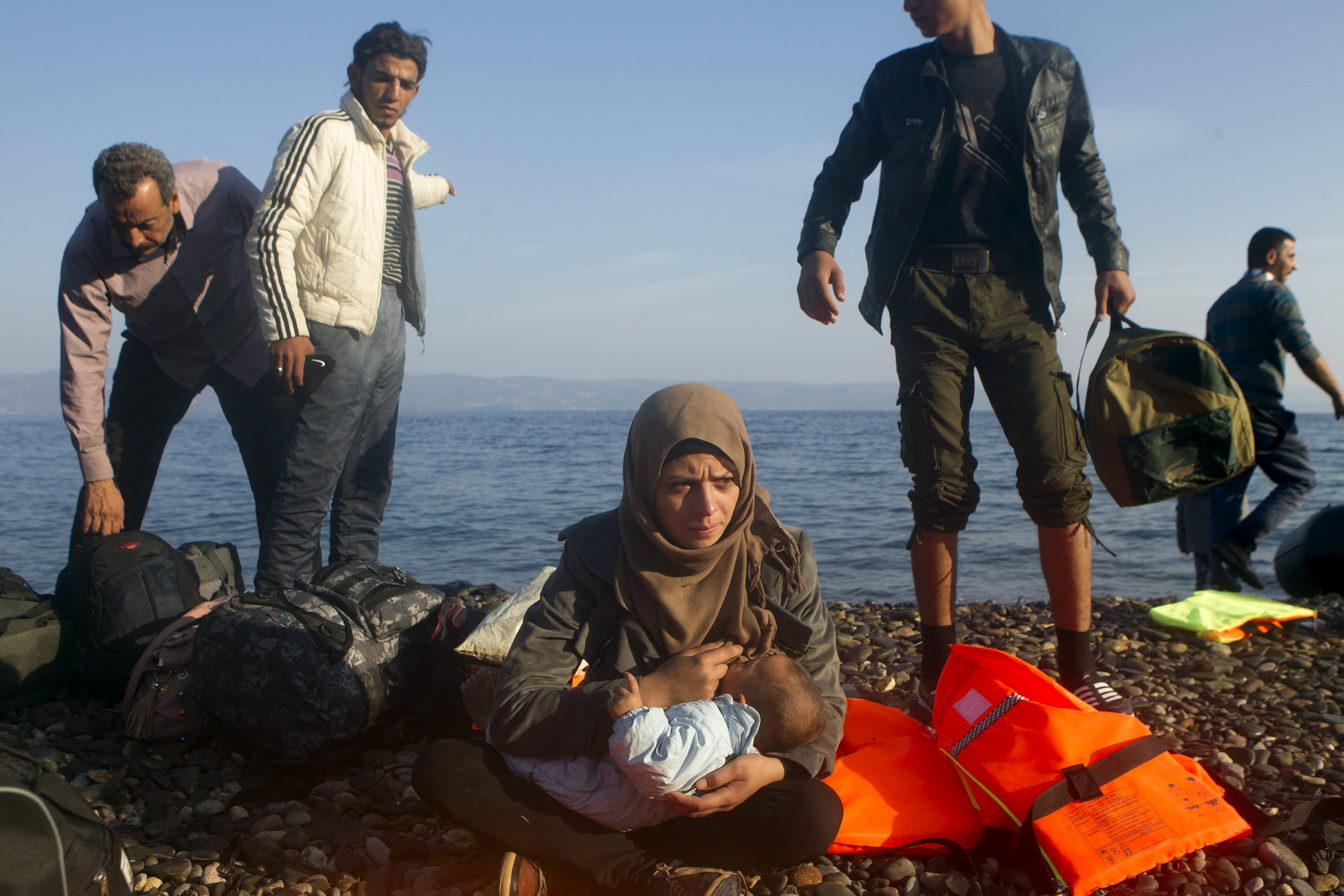 An Iraqi refugee (C) breastfeeds her baby as refugees and migrants arrive on an overcrowded dinghy on the Greek island of Lesbos, after crossing a part of the Aegean Sea from the Turkish coast, October 4, 2015. Refugee and migrant arrivals to Greece this year will soon reach 400,000, according to the UN Refugee Agency (UNHCR). REUTERS/Dimitris Michalakis