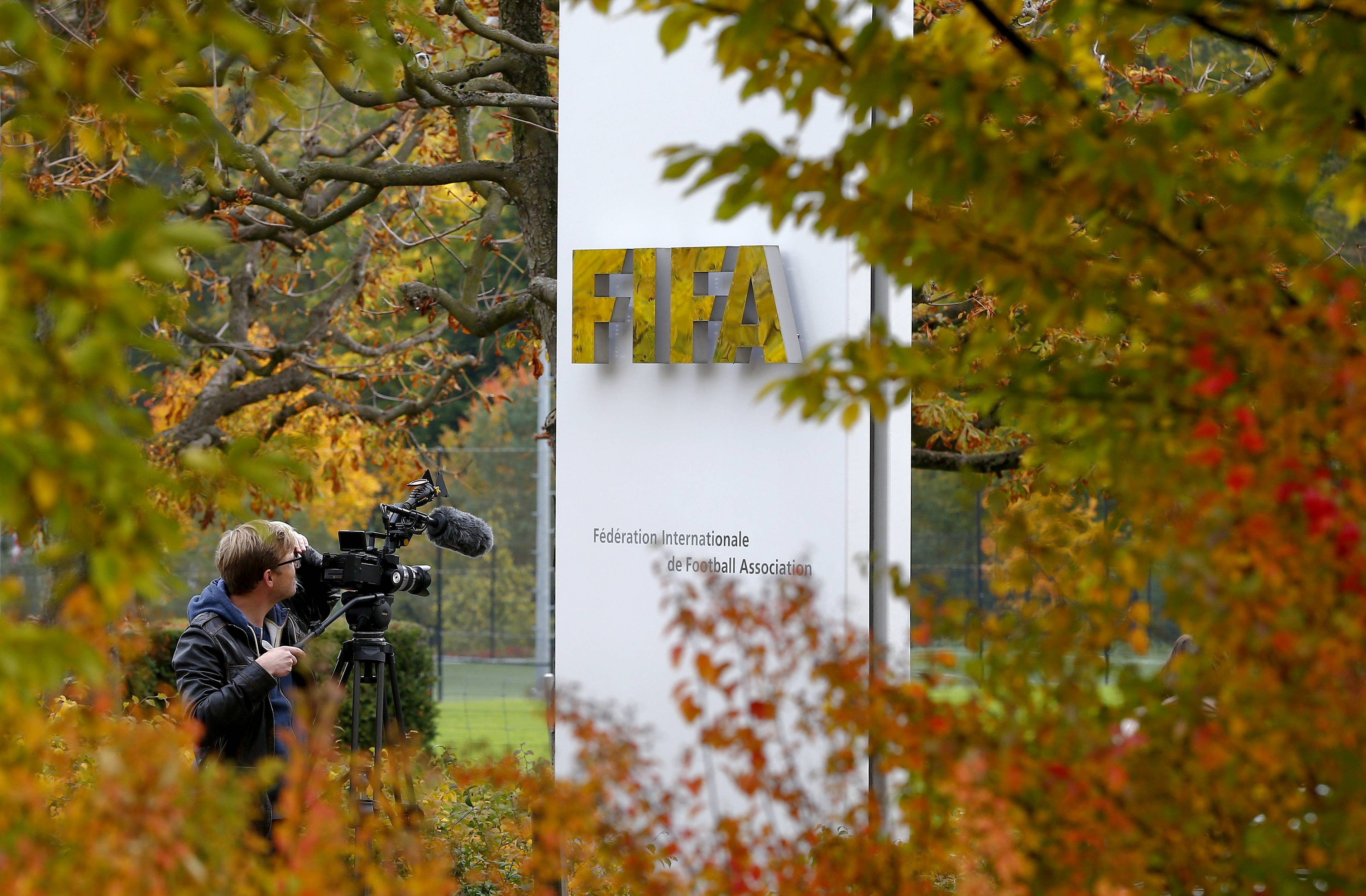 A cameraman stands in front of FIFA's headquarters in Zurich, Switzerland October 8, 2015. FIFA President Sepp Blatter and his possible successor, UEFA chief Michel Platini, have been provisionally suspended for 90 days by the global soccer body's ethics committee. REUTERS/Arnd Wiegmann