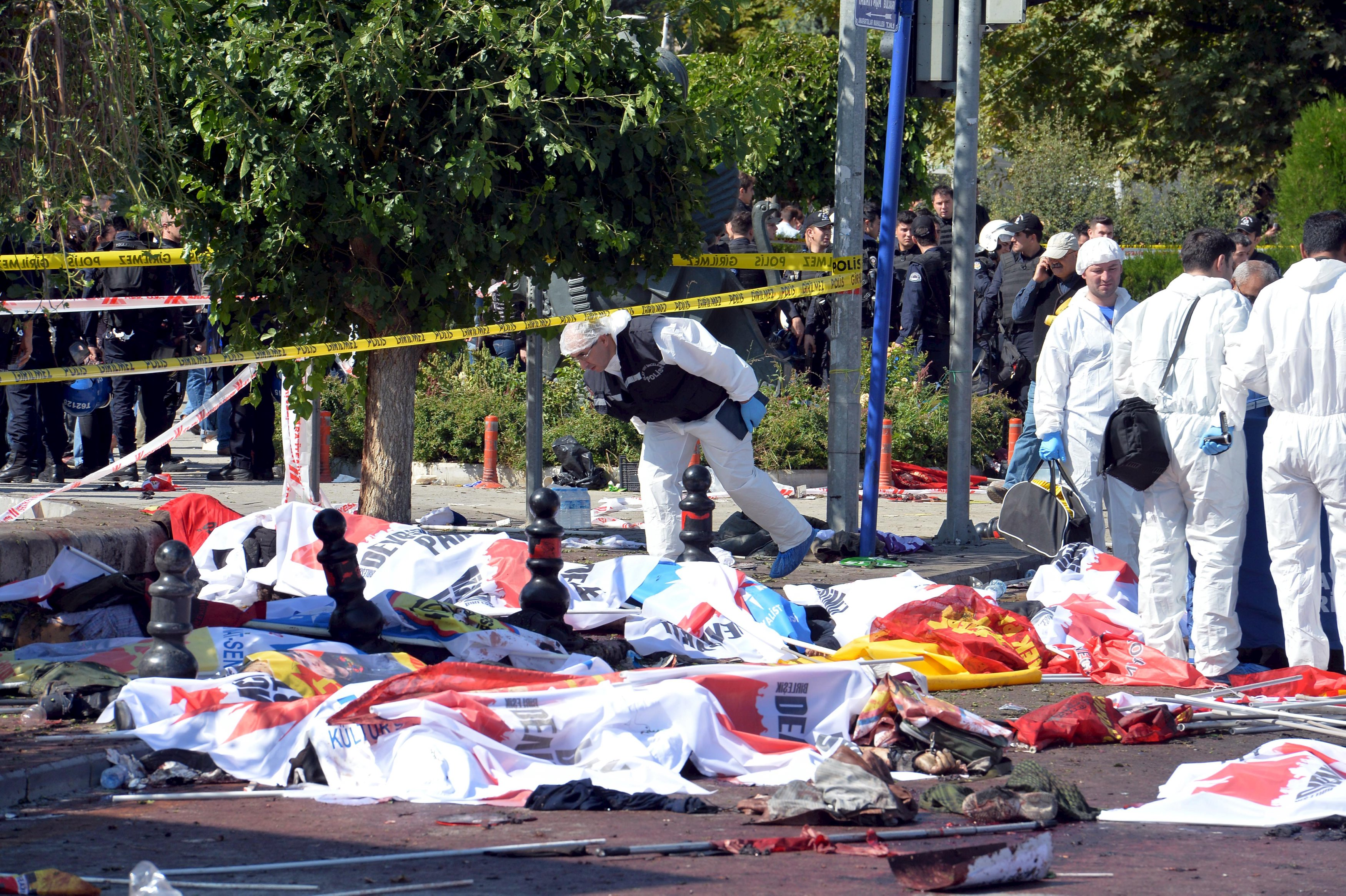 ATTENTION EDITORS - VISUAL COVERAGE OF SCENES OF INJURY OR DEATHPolice forensic experts examine the scene following explosions during a peace march in Ankara, Turkey, October 10, 2015. At least 30 people were killed when twin explosions hit a rally of hundreds of pro-Kurdish and leftist activists outside Ankara's main train station on Saturday in what the government described as a terrorist attack, weeks ahead of an election. REUTERS/Stringer      TPX IMAGES OF THE DAY