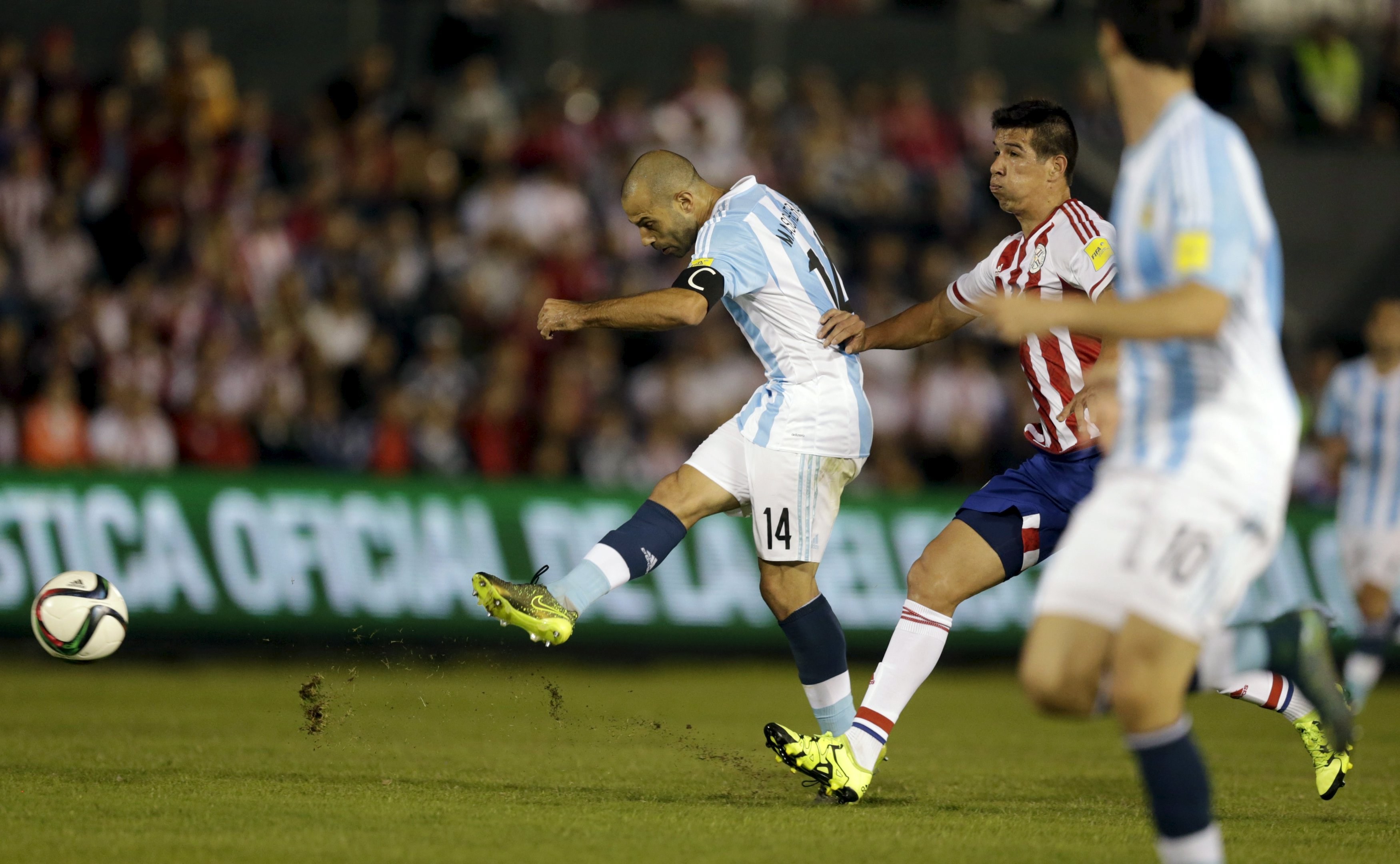 Argentina's Javier Mascherano (L) kicks the ball ahead of Paraguay's Victor Caceres during their 2018 World Cup qualifying soccer match at the Defensores del Chaco stadium in Asuncion, Paraguay, October 13, 2015.      REUTERS/Jorge Adorno
