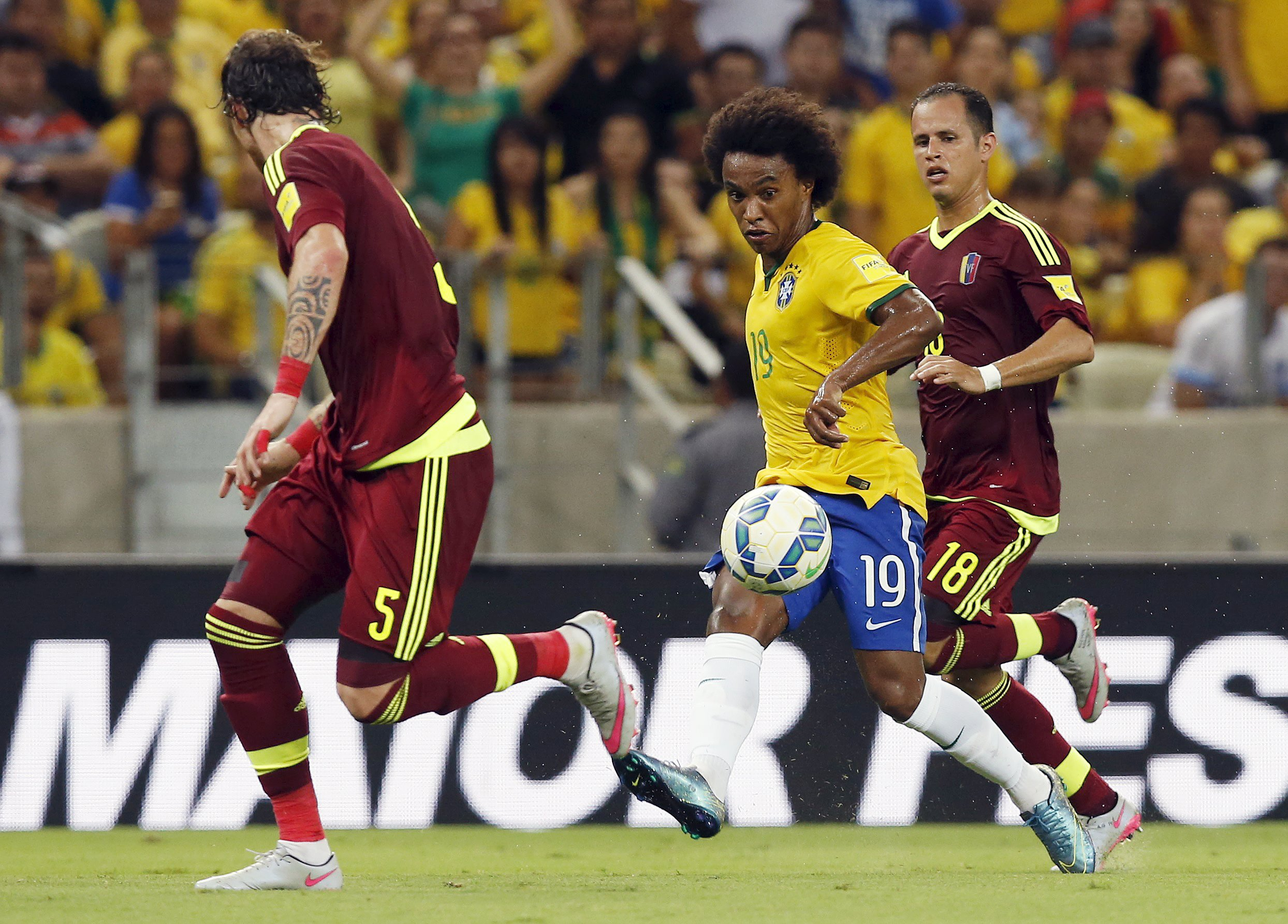 Willian (C) of Brazil kicks the ball between Fernando Amorebieta (L) and Alejandro Guerra of Venezuela during their 2018 World Cup qualifying soccer match in Fortaleza, Brazil, October 13, 2015.   REUTERS/Paulo Whitaker