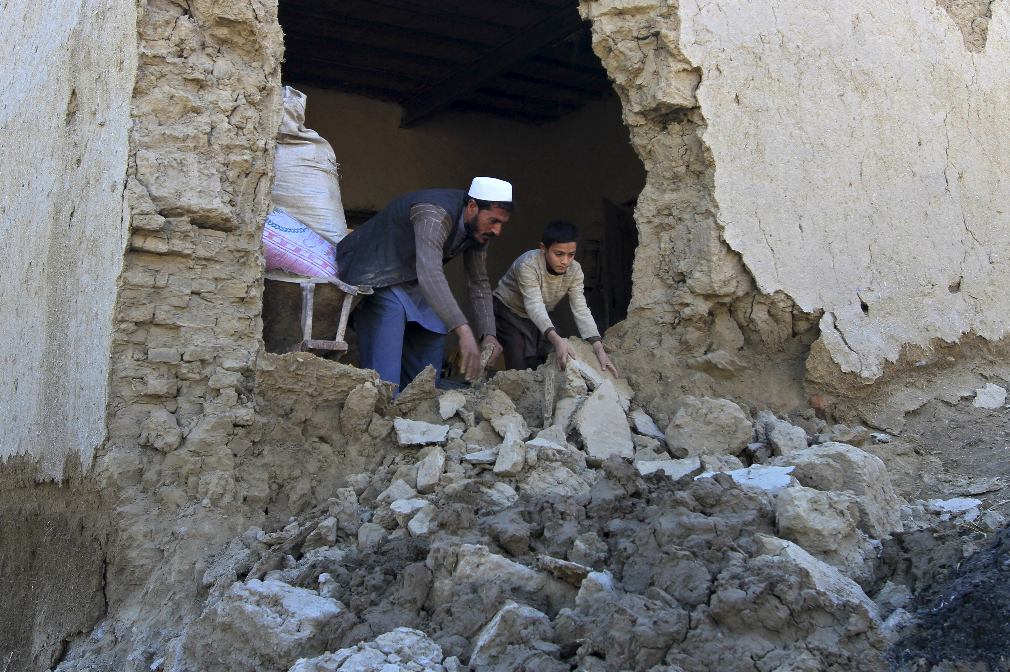 A man and his son clearing rubbles from their house after it was damaged by an earthquake in Behsud district of Nangarhar Province, Afghanistan October 27, 2015. Rescuers on Tuesday rushed to deliver relief aid to victims of a massive earthquake that hit northern Afghanistan and Pakistan. Photo: Reuters