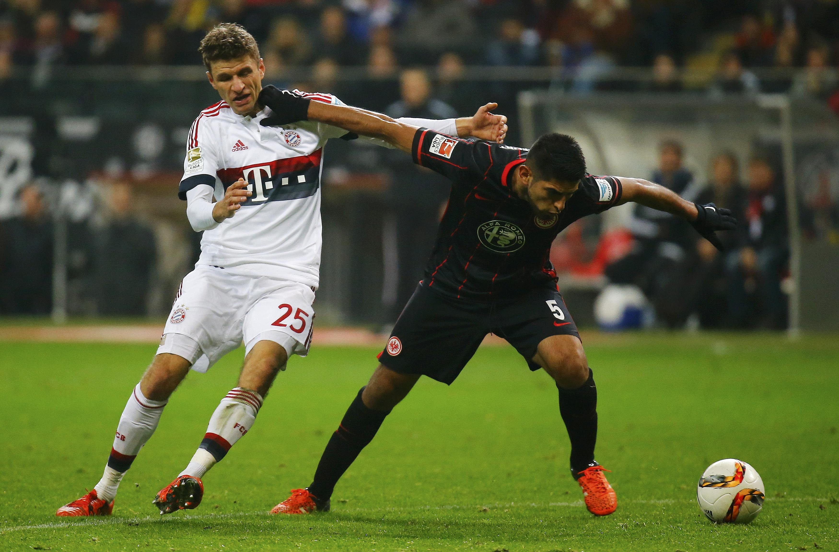 Eintracht Frankfurt's Carlos Zambrano (R) and Bayern Munich's Thomas Mueller fight for the ball during their German first division Bundesliga soccer match in Frankfurt, Germany, October 30, 2015. REUTERS/Kai Pfaffenbach DFL RULES TO LIMIT THE ONLINE USAGE DURING MATCH TIME TO 15 PICTURES PER GAME. IMAGE SEQUENCES TO SIMULATE VIDEO IS NOT ALLOWED AT ANY TIME. FOR FURTHER QUERIES PLEASE CONTACT DFL DIRECTLY AT + 49 69 650050