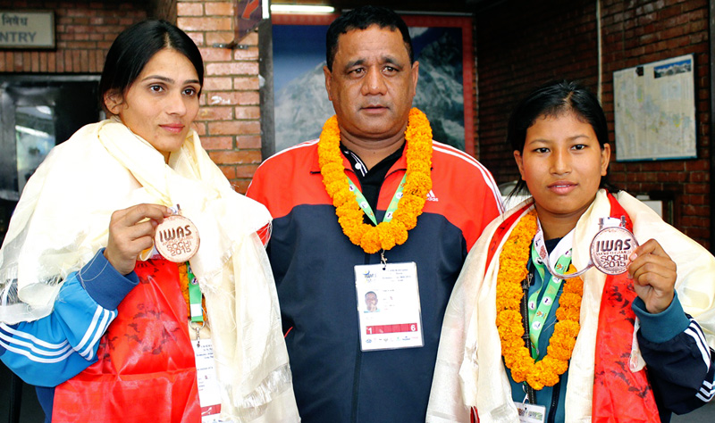 Sit Bhandari (left) and Ranjana Dhami with coach Min Thapa pose for a picture upon arrival their arrival at the Tribhuvan International Airport in Kathmandu on Monday. The Nepali para-taekwondo players Bhandari and Dhami won bronze medals in the World Wheelchair and Amputees Games in Sochi, Russia. Photo: THT
