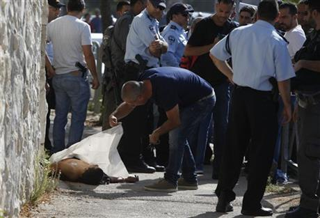 Israeli police stand around the body of a Palestinian in Jerusalem Saturday, Oct. 17, 2015. Police spokeswoman Luba Samri said a 16-year-old Palestinian drew a knife on officers when they approached him in Jerusalem and asked for identification Saturday. She said the officers opened fire and killed him.Photo:AP