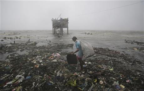 A Filipino man scavenges recyclable materials near a house on stilts stands by the bay as strong winds and rains caused by Typhoon Koppu hit the coastal town of Navotas, north of Manila, Philippines Sunday, Oct. 18, 2015. Photo:AP