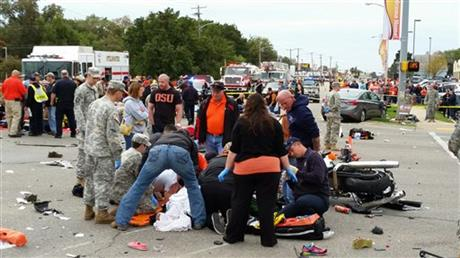 Emergency personnel and spectators respond after a vehicle crashed into a crowd of spectators during the Oklahoma State University homecoming parade, causing multiple injuries, on Saturday, Oct. 24, 2015 in Stillwater, Oka. Phoro: Reuters