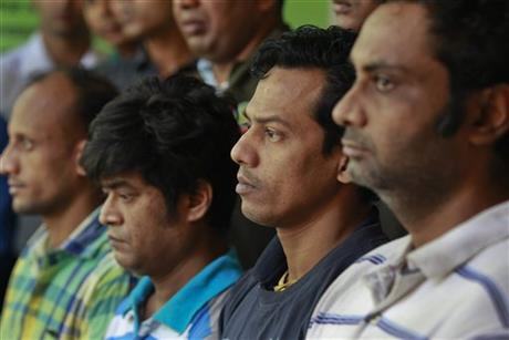 Four suspects arrested by Bangladesh police in the killing of an Italian aid worker last month, stand as they are presented before the media in Dhaka, Bangladesh, Monday, Oct. 26, 2015. Photo: AP
