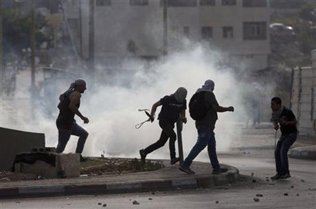 Palestinians run from tear gas during clashes with Israeli troops near Ramallah, West Bank, Monday, Oct. 12, 2015. Recent days have seen a series of stabbing attacks in Israel and the West Bank that have wounded several Israelis. Past weeks have also seen violent demonstrations in the West Bank and Gaza, and at least 16 Palestinians have been killed by Israeli forces. Photo: AP