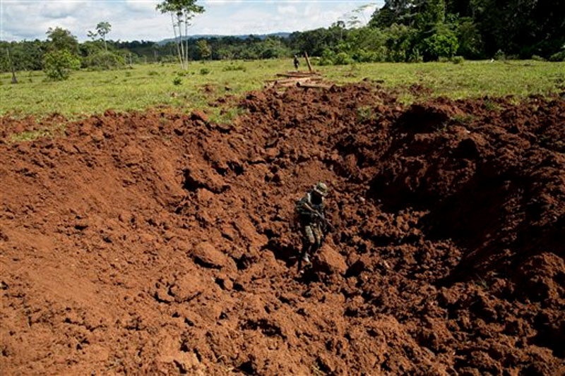 A Peruvian counternarcotics police officer stands in a crater blown into a clandestine airstrip used by cocaine traffickers in Ciudad Constitucion, Peru on July 28, 2015. Photo: AP
