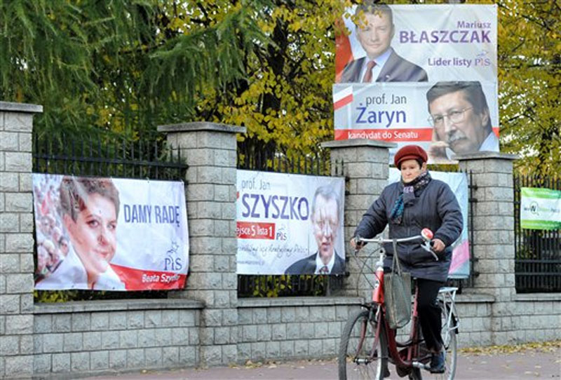 A cyclist drives past Law and Justice election posters, among them Beata Szydlo's first left, in Warsaw, Poland, Monday, October 26, 2015. Photo: AP