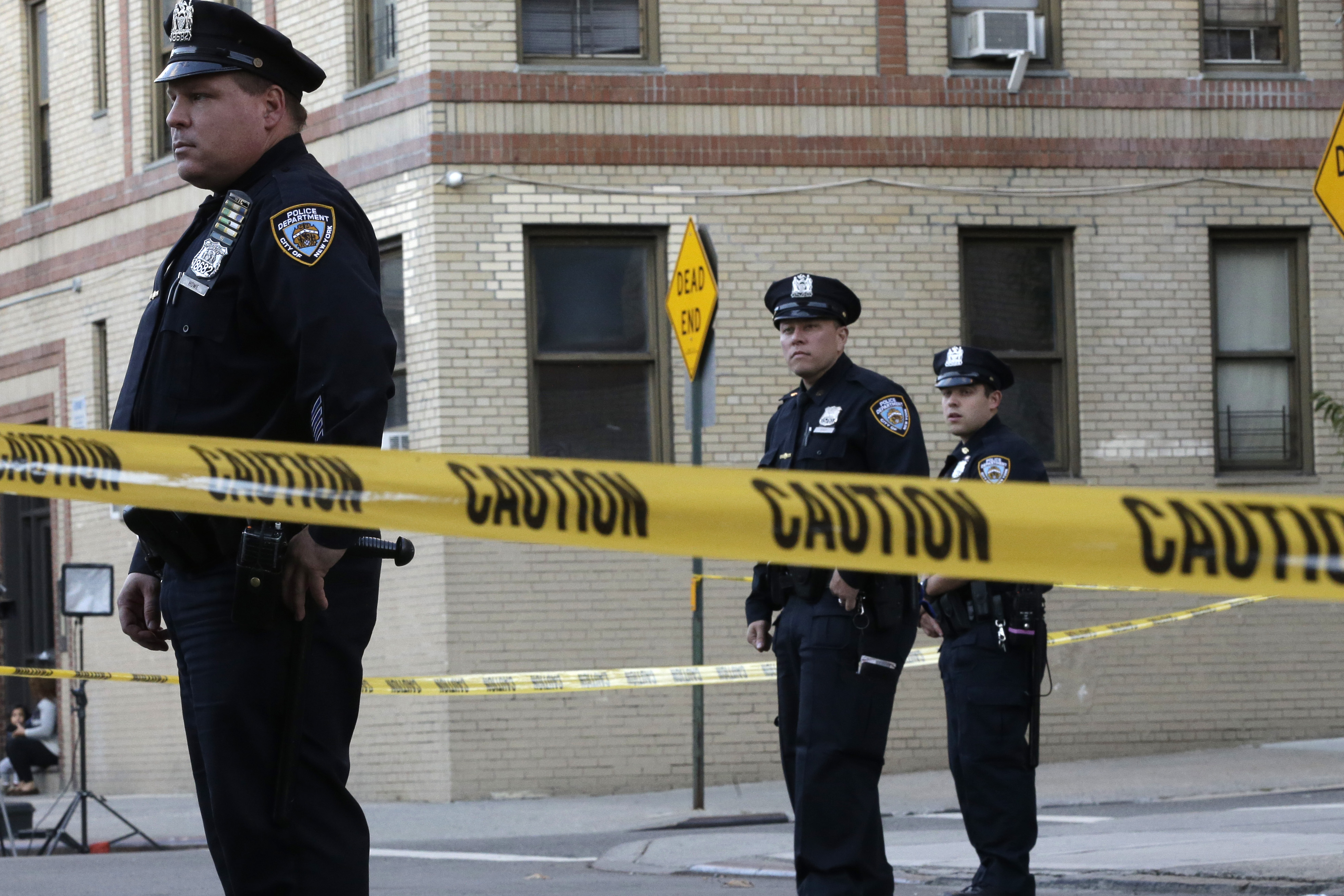Police officers stand guard near an apartment building in the Bronx borough of New York, on Thursday, October 15, 2015. Photo: AP