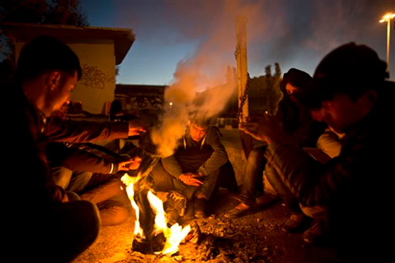 Afghan refugees gather around a fire to warm themselves from the morning cold at the port of Mitylene on the northeast Greek island of Lesbos, while waiting to get on board a ferry traveling to Athens, early Friday, Oct. 9, 2015. Photo: AP