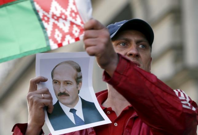 A man holds a portrait of Belarussian President Alexander Lukashenko, who is a candidate in the upcoming presidential elections, and a Belarussian national flag during a meeting between opposition leaders and people, in central Minsk, September 10, 2015. REUTERS/Vasily Fedosenko/Files