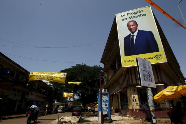 A poster of Guinea's outgoing president and presidential candidate Alpha Conde, leader of Rassemblement du Peuple de Guinea (RPG) is seen at a junction of Kaloum in Conakry, October 8, 2015. Guinea will hold its presidential election on Sunday. REUTERS/Luc Gnago