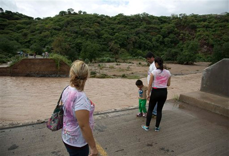 People stand at the edge of a collapsed bridge, overlooking the Ameca River in Cofradia, some 200 km northwest of Guadalajara, Mexico, Saturday, October 24, 2015. Photo :AP