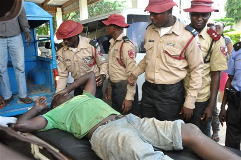 An injured man is helped following a bomb explosion at the site of a bomb explosion in Nyanya outskirt of Abuja, Nigeria, Saturday, October 3, 2015. Photo: AP