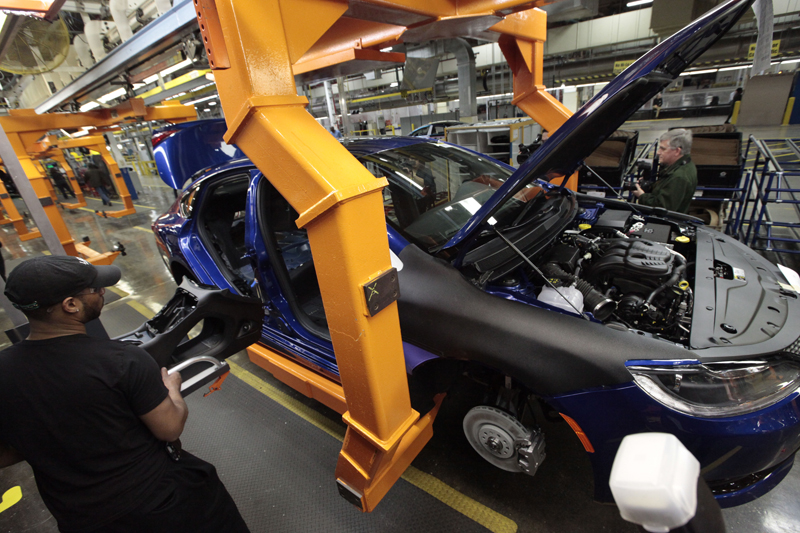 FILE - In this March 14, 2014, file photo, an assembly line worker builds a 2015 Chrysler 200 automobile at the Sterling Heights Assembly Plant in Sterling Heights, Mich. Fiat Chrysler's U.S. sales jumped 14 percent in September 2015, helped in part by another strong month from the carmaker's Jeep brand. (AP Photo/Paul Sancya, File)