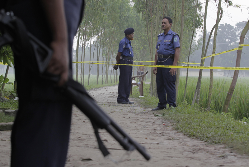 Bangladeshi security officers stand by the site where a Japanese Kunio Hoshi was killed at Mahiganj village in Rangpur district, 300 kilometers (185 miles) north of Dhaka, Bangladesh, Sunday, Oct. 4, 2015. Masked assailants riding a motorbike shot and killed Kunio Hoshi on Saturday, police said. The Islamic State group issued a statement claiming responsibility for the attack, according to the SITE Intelligence Group, which monitors jihadi postings online. The report could not be independently confirmed. The extremist group also claimed responsibility for the killing of an Italian aid worker last Monday. (AP Photo/A.M. Ahad)