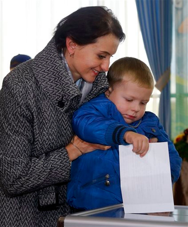 A Belarusian woman with her son casts a ballot at a polling station during presidential elections in Minsk, Belarus, Sunday, October 11, 2015. Photo: AP