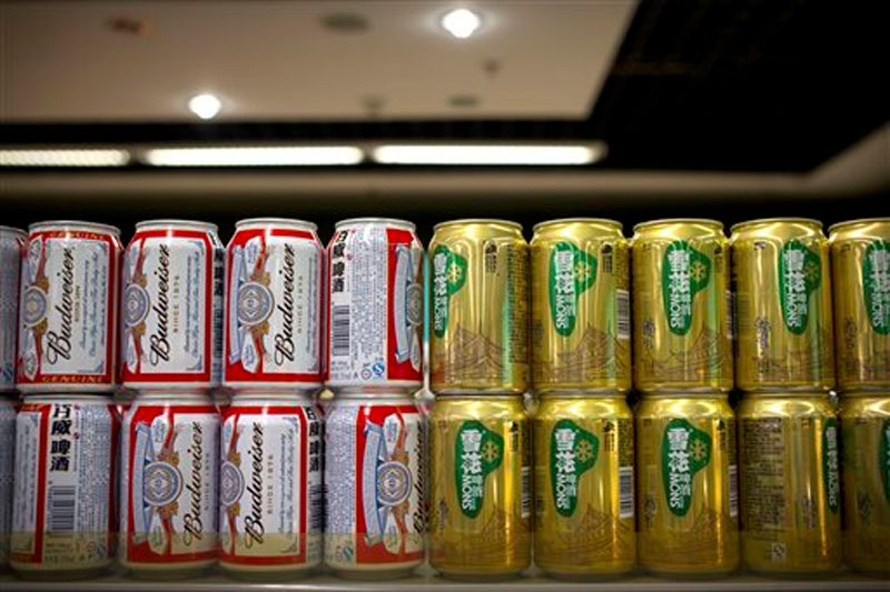 Cans of Budweiser beer, owned by AB InBev, sit next to cans of Snow beer, in which SABMiller has a 49 percent ownership stake, on a grocery store shelf in Beijing on Thursday, Oct. 15, 2015. Photo: AP