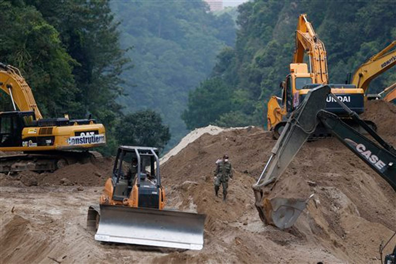 Bulldozers move land for a fourth day to search for victims of a fatal mudslide in Cambray, a neighborhood in the suburb of Santa Catarina Pinula, on the outskirts of Guatemala City, Monday, October 5, 2015. Photo: AP
