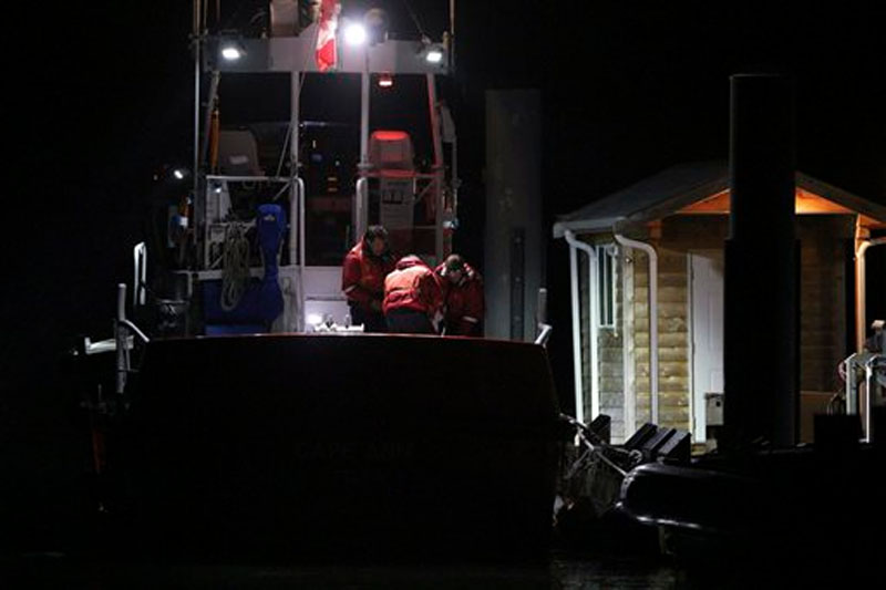 Canadian Coast Guard crew arrive at a dock in Tofino, west coast of Vancouver, Canada, early Monday, October 26, 2015, following a search and rescue operation.