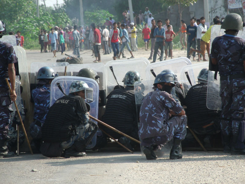 Nepal Police personnel shield themselves from protesters as a clash ensued between them in Chandranigahapur of Rautahat on Friday, October 2, 2015. Photo: Prabhat Kumar Jha