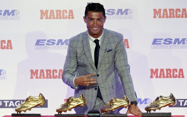 Real Madrid's striker Cristiano Ronaldo poses in front of his four Golden Boot trophies during a ceremony in Madrid, Spain, October 13, 2015. REUTERS/Andrea Comas