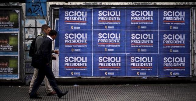 People walk next to posters advertising presidential candidate Daniel Scioli in Buenos Aires October 19, 2015. REUTERS/Marcos Brindicci