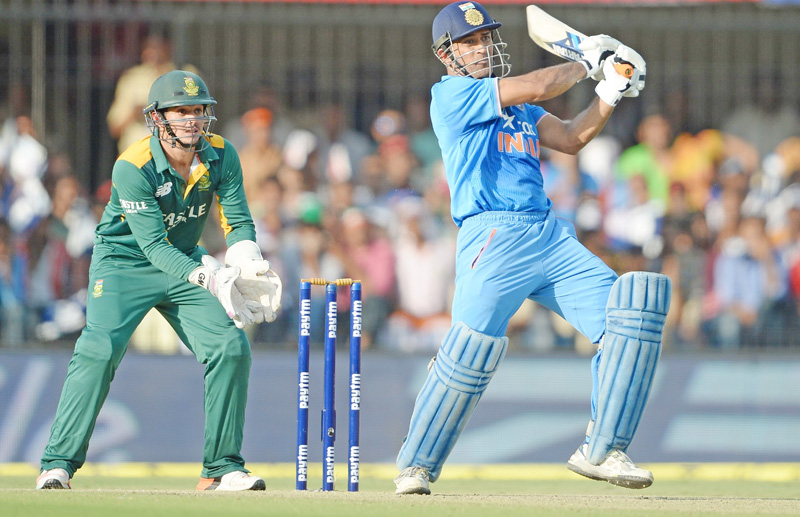 India's Mahendra Singh Dhoni plays a shot as South Africa's Quinton de Kock looks on during their second ODI match at the Holkar Cricket Stadium in Indore on Wednesday. Photo: AFP