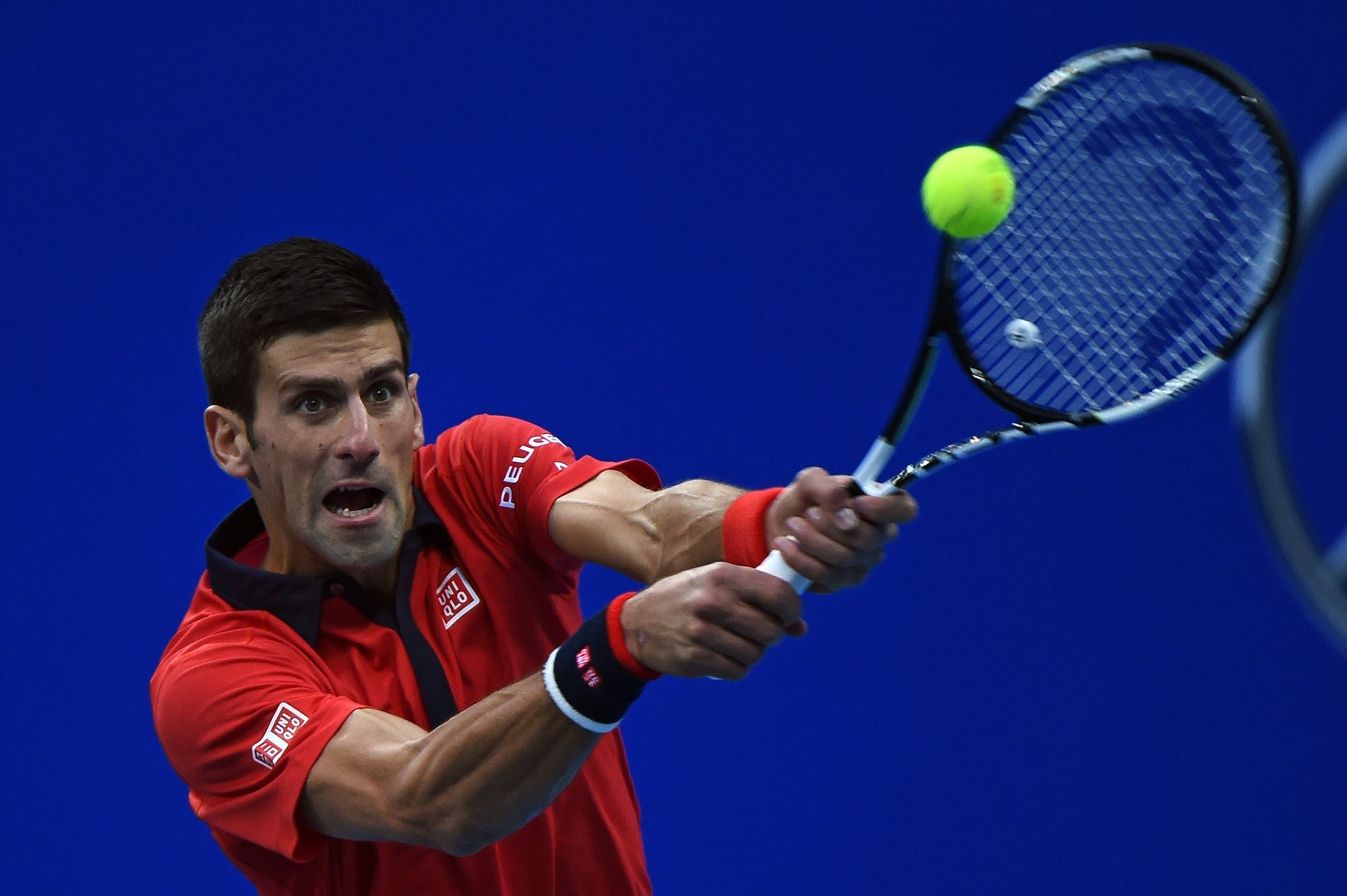 Novak Djokovic of Serbia hits a return against Zhang Ze of China during their men's singles second round match at the China Open tennis tournament in Beijing on October 8, 2015. AFP PHOTO / GREG BAKER