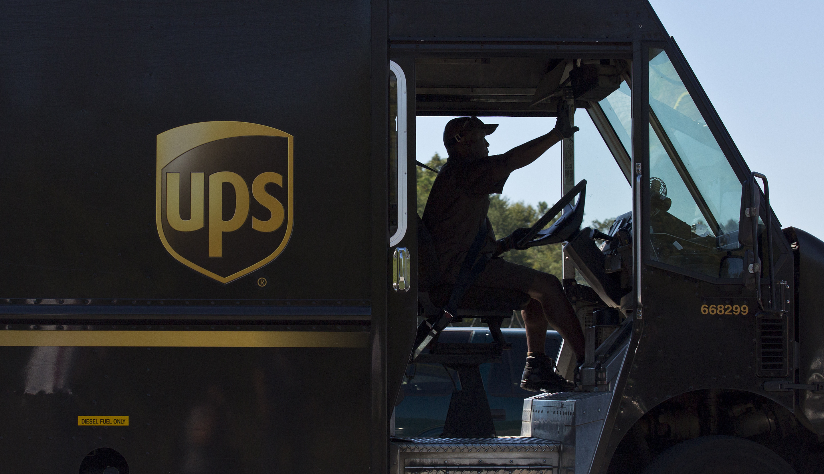 FILE - In this Sept. 23, 2014 file photo, a United Parcel Service (UPS) truck driver enters a company warehouse in Birmingham, Ala. UPS reports quarterly financial results before the market opens on Tuesday, Oct. 27, 2015. (AP Photo/Brynn Anderson, File)