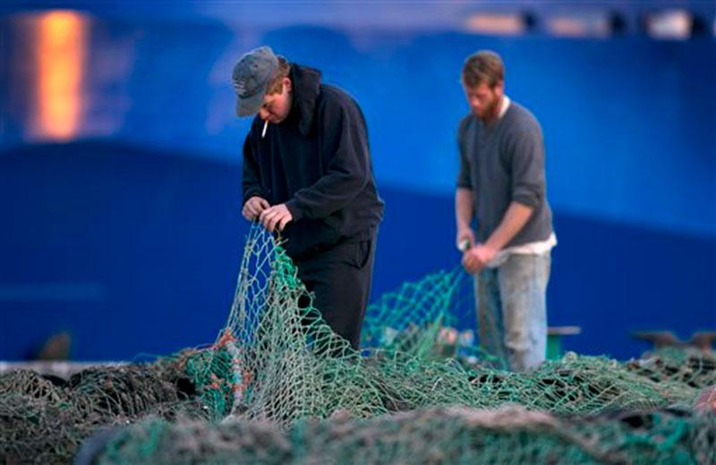 Fishermen Ed Stewart (left) and Tannis Goodsen mend groundfishing nets on Merrill Wharf in Portland, Maine on November 15, 2013. Photo: AP