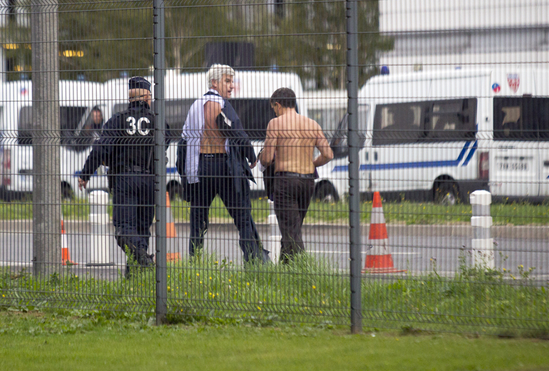 Air France director of Human Ressources, Xavier Broseta, right, and Air France assistant director long-haul flight, Pierre Plissonnier, center, are protected by a police officer as they flee Air France headquarters at Roissy Airport, north of Paris, after scuffles with union activist, Monday, Oct. 5, 2015. Photo: AP