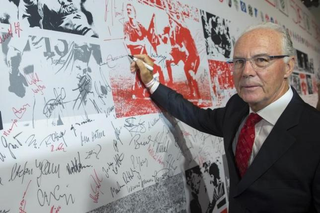 Former player and coach Franz Beckenbauer signs a wall of fame at a gala marking the 50th anniversary of the foundation of the German Bundesliga soccer league, in Berlin August 6, 2013.  REUTERS/Thomas Peter/Files
