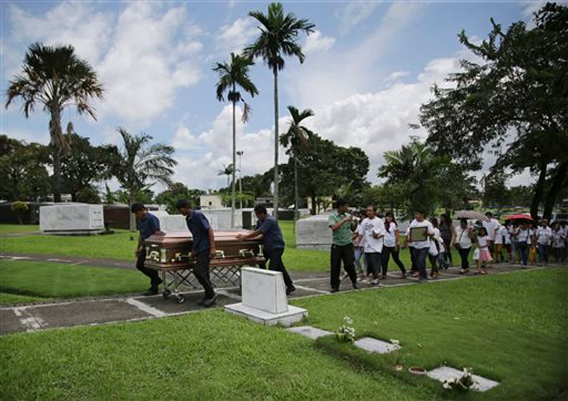 Funeral workers carry the casket of American Nobel laureate for chemistry Richard Heck as relatives and friends attend burial rites in suburban Quezon city, north of Manila, Philippines Tuesday, Oct. 13, 2015.