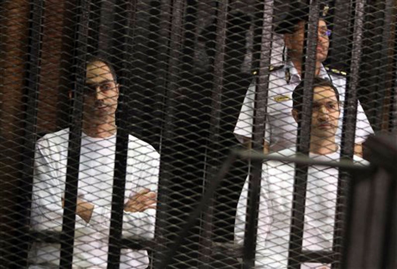 Gamal Mubarak (left) and his brother Alaa Mubarak, sons of ousted Egyptian President Hosni Mubarak, listens to court proceedings from the defendants' cage in a courtroom in Cairo, Egypt on July 9, 2012. Photo: AP