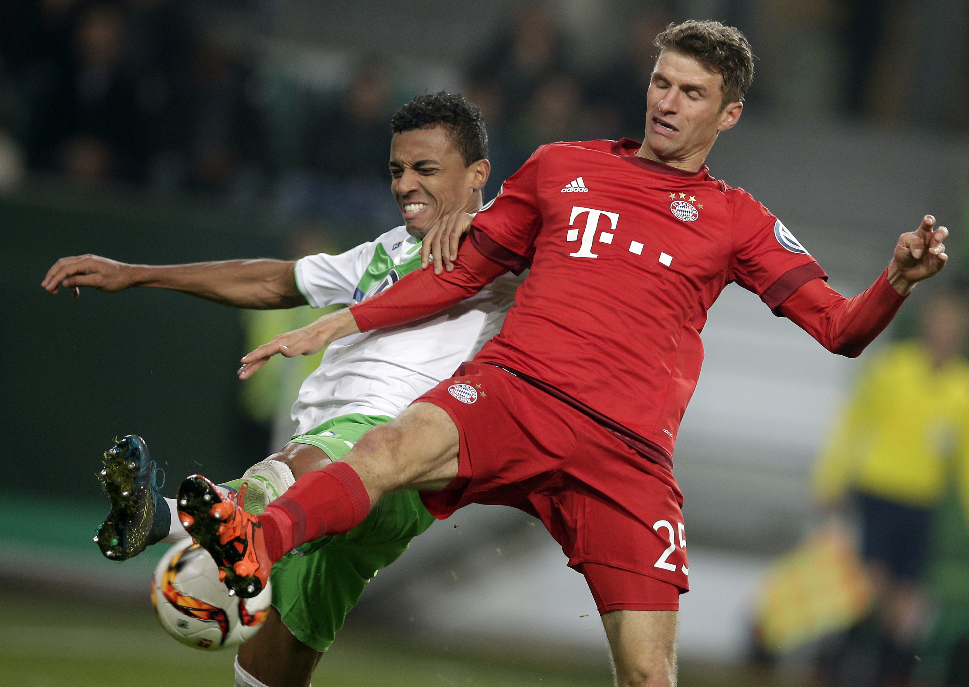 Wolfsburg's Luiz Gustavo, left, and Bayern's Thomas Mueller, right, challenge for the ball during the German soccer cup second round match between VfL Wolfsburg and FC Bayern Munich in Wolfsburg, Germany, Tuesday, Oct. 27, 2015. (AP Photo/Michael Sohn)