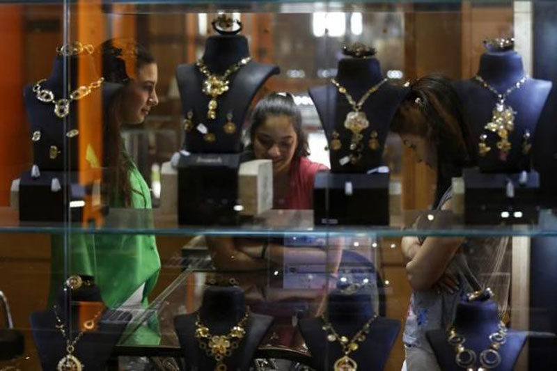 Customers look at gold accessories displayed at a jewellery shop in Amman, Jordan July 27, 2015. Reuters