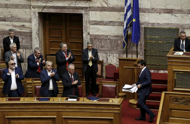 Greek Prime Minister Alexis Tsipras acknowledges applause from ministers of his government following his speech during a parliamentary session before a vote of confidence at the parliament building in Athens, Greece, October 8, 2015.  REUTERS/Alkis Konstantinidis