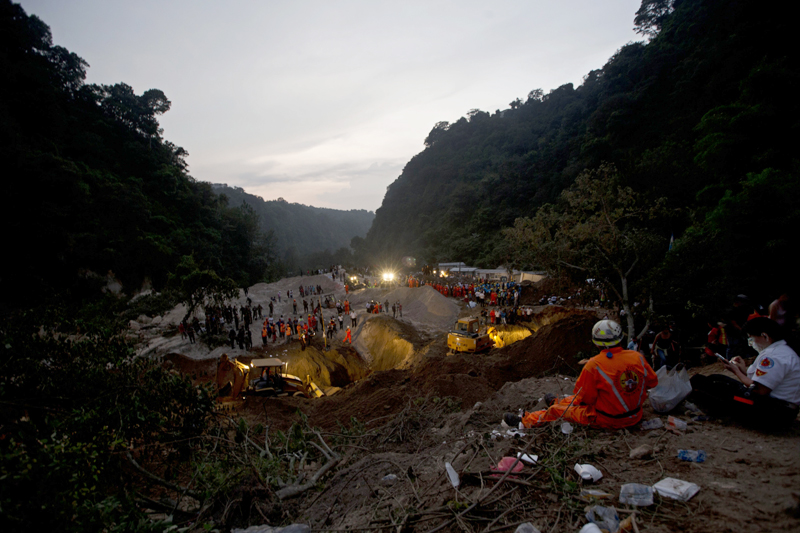 Rescue workers and firemen continue their search for survivors at the the site of a landslide in Cambray, a neighborhood in the suburb of Santa Catarina Pinula, about 10 miles east of Guatemala City, Friday, Oct. 2, 2015. The hill that towers over Cambray collapsed late Thursday after heavy rains, burying several houses with dirt, mud and rocks. (AP Photo/Moises Castillo)
