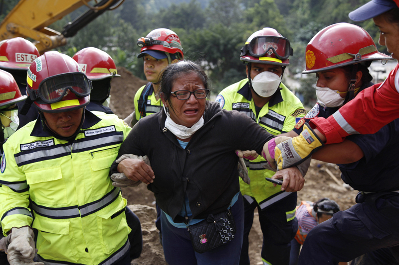 Rescue workers help a woman after she identified two family members as their bodies are retrieved from the site of a mudslide in Cambray, a neighborhood in the suburb of Santa Catarina Pinula, on the outskirts of Guatemala City, Saturday, Oct. 3, 2015. Rescue workers recovered more bodies Saturday after a hillside collapsed on homes late Thursday, while more are feared still buried in the rubble. (AP Photo/Luis Soto)