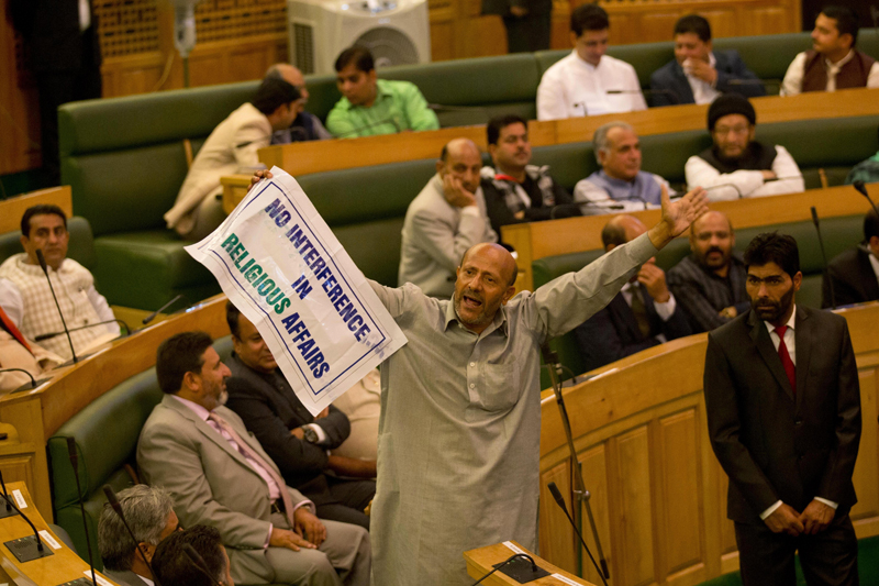 Engineer Rashid, an independent legislator, holds a banner as he disrupts the first day of Jammu and Kashmir stateu0092s autumn assembly session in Srinagar, Indian controlled Kashmir, Saturday, Oct. 3, 2015. Rashid was protesting a court ruling upholding a colonial-era law banning cow slaughter and the sale of beef in the Indian-controlled portion of Kashmir. (AP Photo/Dar Yasin)
